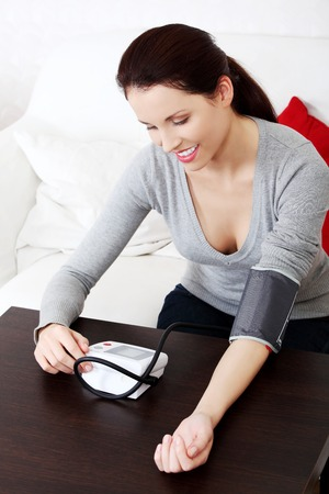 ilness: Beautiful woman is measuring her blood pressure. Ilness concept.