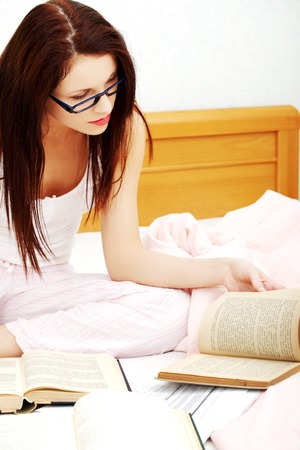 Woman is note something from the books in bed. Working or studing concept. photo