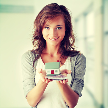 Beautiful young woman holding euros bills and house mode- real estate loan concept Stock Photo - 28759749