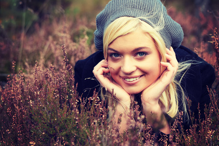 lieing: Young caucasian blonde in grey cap lieing in heather