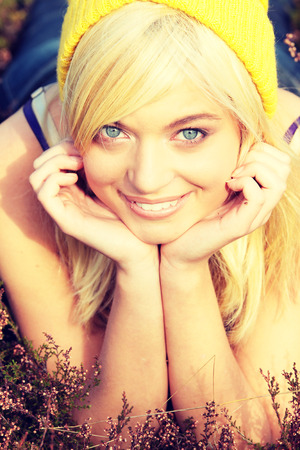 lieing: Young caucasian blonde in yellow cap lieing in heather
