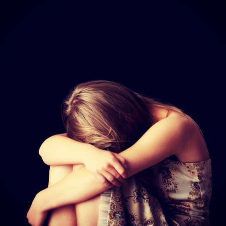 tormented: Young woman depression isolated on black background