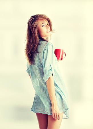 The beautiful young woman drinks morning coffee or tea Stock Photo - 28760379