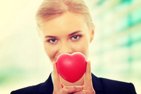 bondad: Mujer de negocios joven sosteniendo el corazón en forma de juguete  Foto de archivo