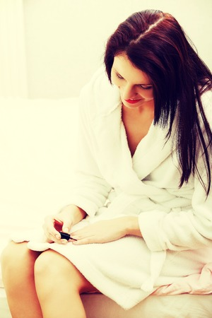 Portrait of a beautiful fit woman painting her mails in the morning, while sitting on the bed being dressed in a dressing-gown. photo