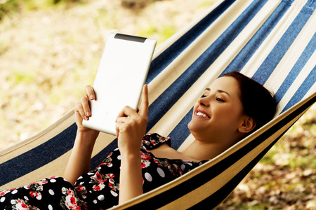 Woman Relaxing In Hammock With  Tablet computer photo