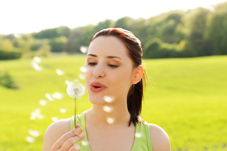 with pollen: Woman blowing on a dandelion.