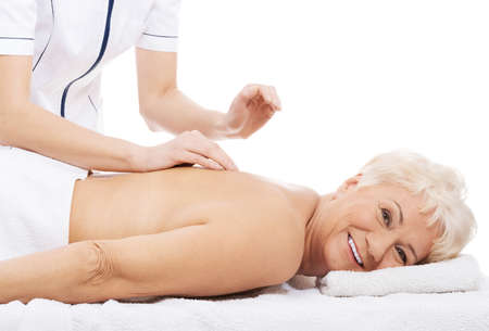 Old woman is having a massage. Spa concept. photo