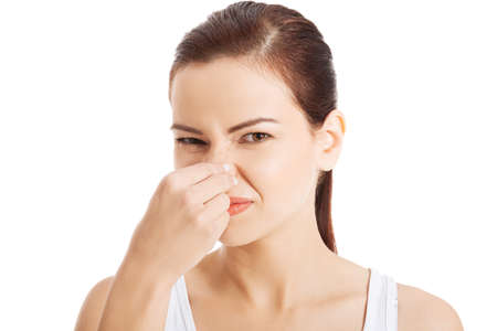Portrait of a young woman holding her nose because of a bad smell. photo