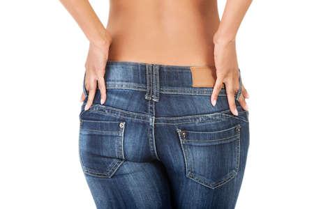 tight jeans: Una mujer atractiva joven lleva los pantalones vaqueros azules. Vista trasera. Foto de archivo