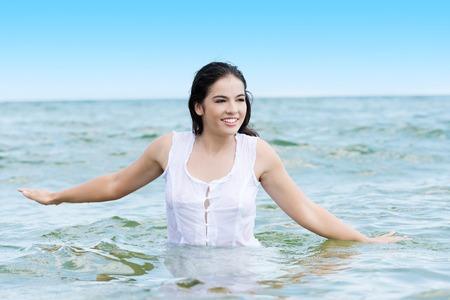 Summer happy woman in water, wearing white dress.