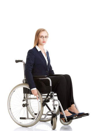 Sad, serious business woman sitting on wheelchair. Isolated on white. photo