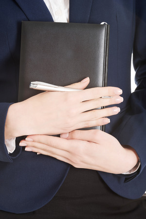 close uo: Close uo on notebook and pen in business womans hands.