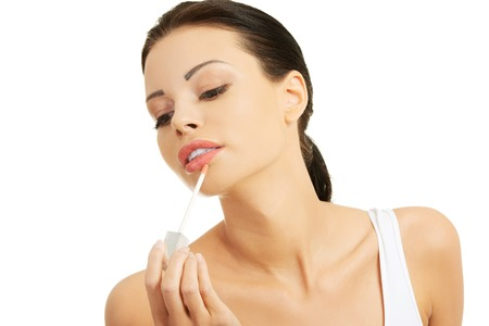 light complexion: Woman putting on lip gloss