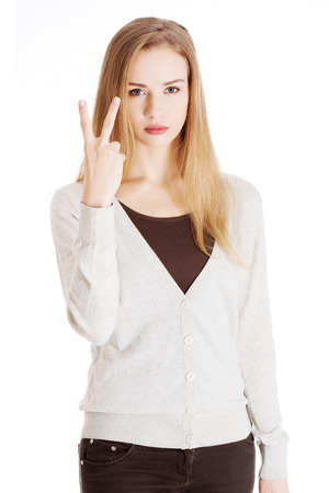 Beautiful casual woman is showing victory sign, two fingers. Isolated on white. photo