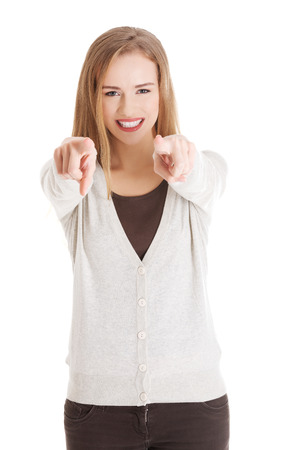 Beautiful casual woman pointing on you, advertising. Isolated on white. photo