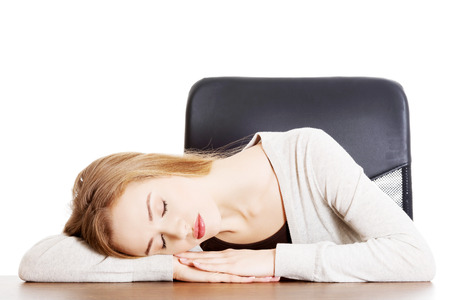 Young casual woman student is sleeping on a desk. Isolated on white. photo