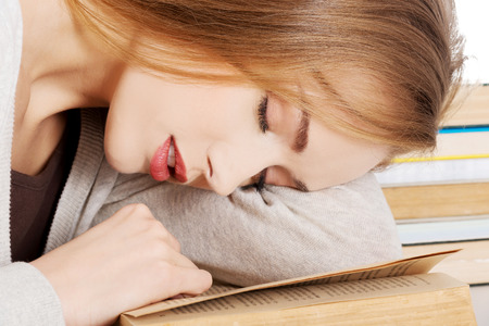 Beautiful woman is sleeping on a book. Student and education concept. Isolated on white. photo
