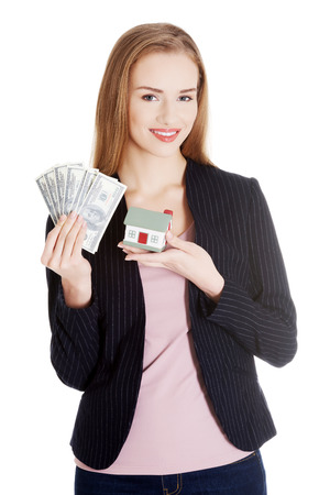 Beautiful business woman holding dollar currency and house. Isolated on white. photo