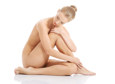 Beautiful caucasian naked woman sitting with fresh clean skin. Isolated on white. Stock Photo