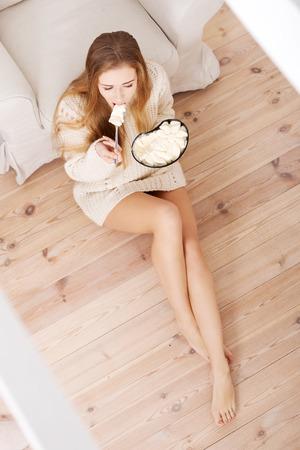 Happy caucasian woman is eating ice cream. Indoor background. photo