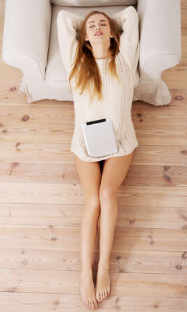 Beautiful caucasian woman sitting on the wooden floor with tablet. photo