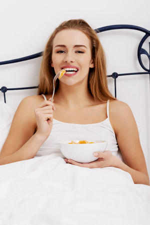 Beautiful caucasian woman eating fresh fruit for breakfast in bed. photo