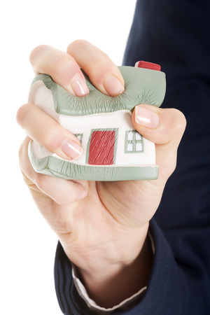 House model being squeezed in womans hand. Over white background. photo