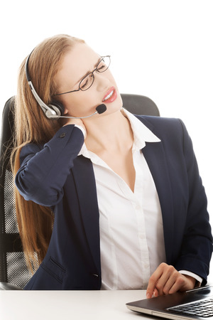 back ache: Beautiful business woman at call center is having back ache. Isolated on white.
