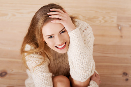 careless: Picture of a careless young caucasian woman on the wooden floor wearing bright sweater.