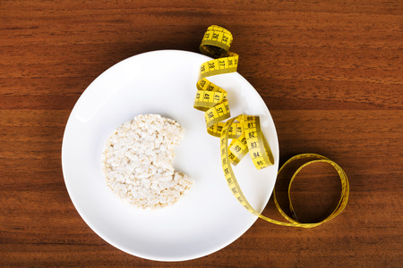 One waffle rice on a plate and measuring tape. Over wooden background. photo