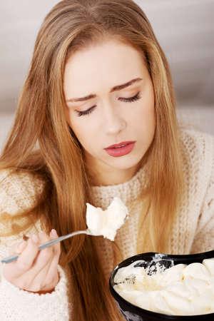 mujeres tristes: Joven mujer deprimida está comiendo gran tazón de helado de consolarse. La depresión, la bulimia y el concepto de dieta.