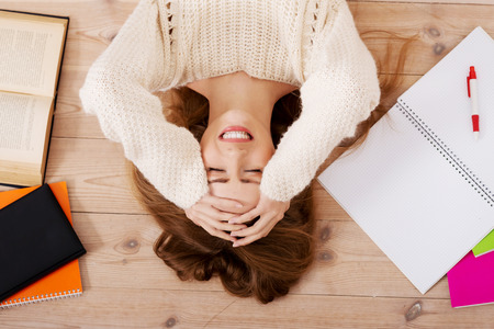 Young beautiful woman lying on the wooden floor with books. photo