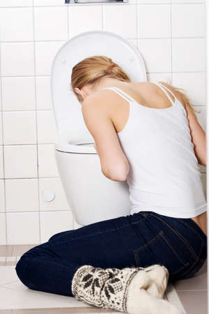 Young caucasian woman is vomiting in the bathroom. Bulimia, sick concept. photo