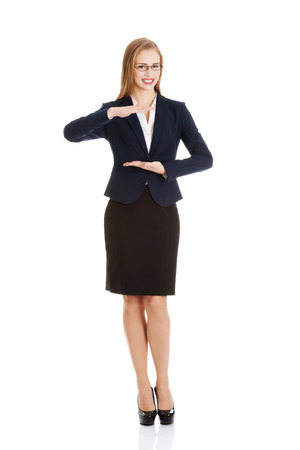 Beautiful business woman holding empty copy space between her hands. Isolated on white. photo