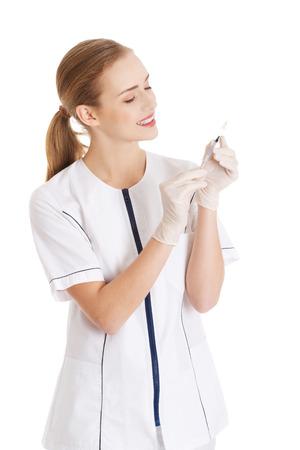 Beautiful young nurse with needle. Isolated on white. photo