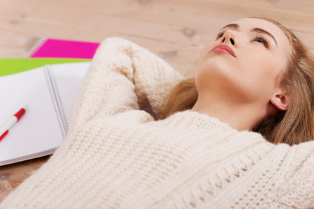 Young beautiful student woman is lying on the wooden floor around books. photo
