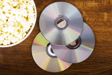 Picture of popcorn in a bowl and CDs lying on table. photo