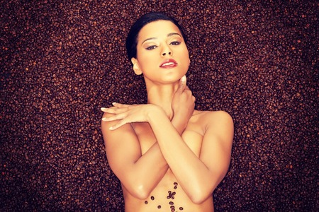 Attractive naked woman lying in coffee grains. Up front view. photo