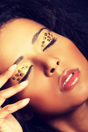 Close up on beautiful tiger make-up on eyes. Goldis-blakish eyeshadows. photo