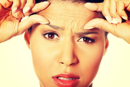 wander: Woman checking her wrinkles on her forehead. Stock Photo