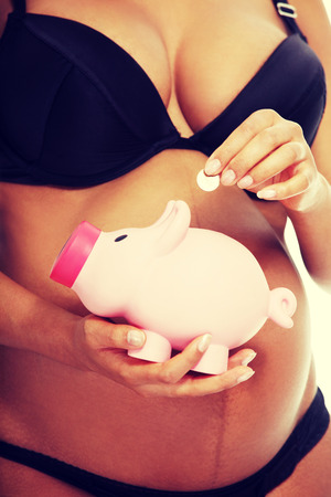 Young beautiful pregnant woman holding a pink piggybank in front of her belly photo