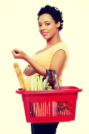 Pregnant woman with shopping basket. photo