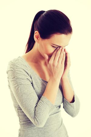 aching: Young beautiful woman touching her nose