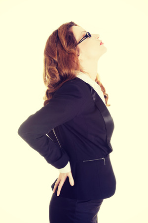 Business woman with back pain after long work on chair. photo