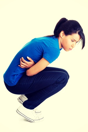 aching: Young woman with stomach issues. Stock Photo