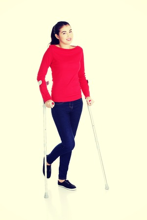immobility: Woman walking with crutches becouse of leg injury