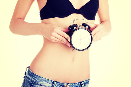 Beautiful fit belly woman with clock on belly Stock Photo
