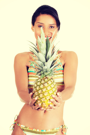 Happy summer woman in bikini with pineapple photo