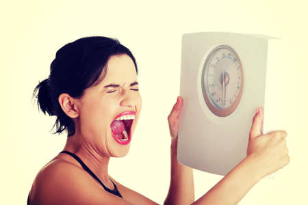 weight control: Frustrated young woman with scale.